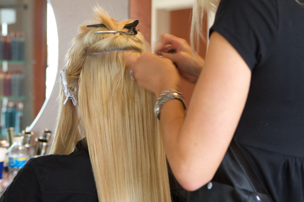 Image of a hairdresser applying extensions to a client's hair.